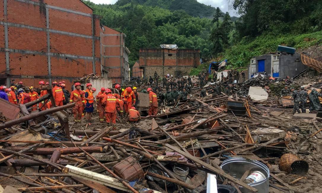 Equipes de resgate procuram sobreviventes nos destroços de prédios atingidos por deslizamento causado pela chuva torrencial na passagem do tufão Lekima, em Yongjia, em Wenzhou, na província de Zhejiang, China Foto: STR / AFP
