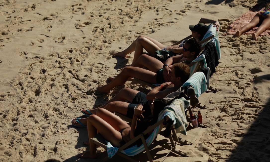 Com os termômetros registrando o calor que aqueceu a cidade neste sábado, todo pedaço de sol na areia era disputado Foto: Brenno Carvalho / Agência O Globo
