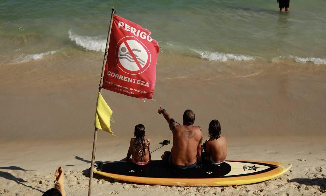 O mar em Ipanema estava com bandeira vermelha, registrando o perigo de correnteza forte. Os avisos são postos pelos bombeiros todas as manhãs, orientando os banhistas Foto: Brenno Carvalho / Agência O Globo