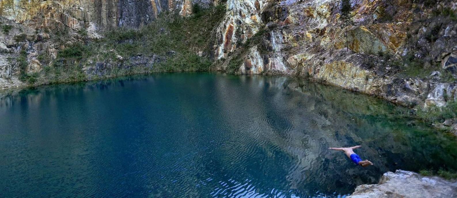 Brincando com a sorte: jovem mergulha na atraente Lagoa Azul, área de Tanguá, de onde mineradora, que deixou o local há cinco anos, extraía metais usados na indústria siderúrgica Foto: Márcio Alves / Agência O Globo