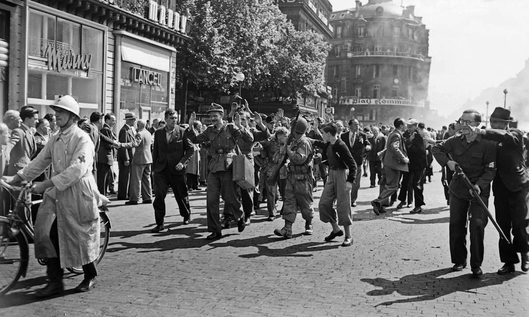 Em 25 de agosto de 1944, combatentes armados da FFI (Forças Francesas do Interior) escoltam soldados alemães após rendição e a tomada do edifício Kommandantur na Place de l'Opera em Paris, durante a batalha pela Libertação de Paris, durante a Segunda Guerra Mundial Foto: - / AFP