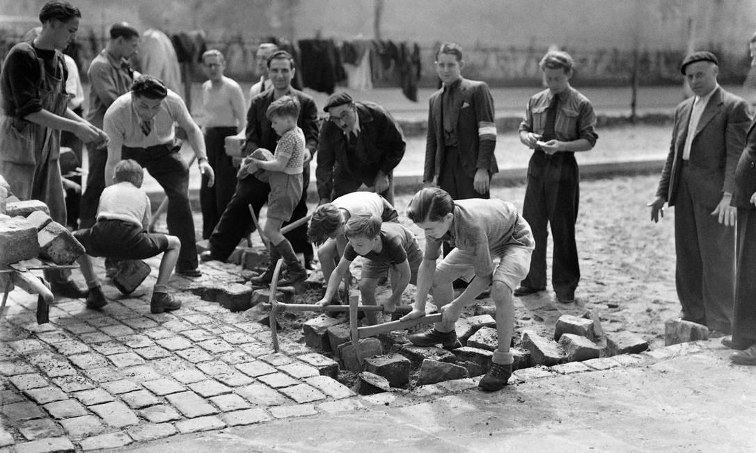 Crianças parisienses e membros da FFI constroem uma barricada em uma rua de Paris, durante a batalha pela Libertação da capital da França, durante a Segunda Guerra Mundial, em 22 de agosto de 1944 Foto: - / AFP