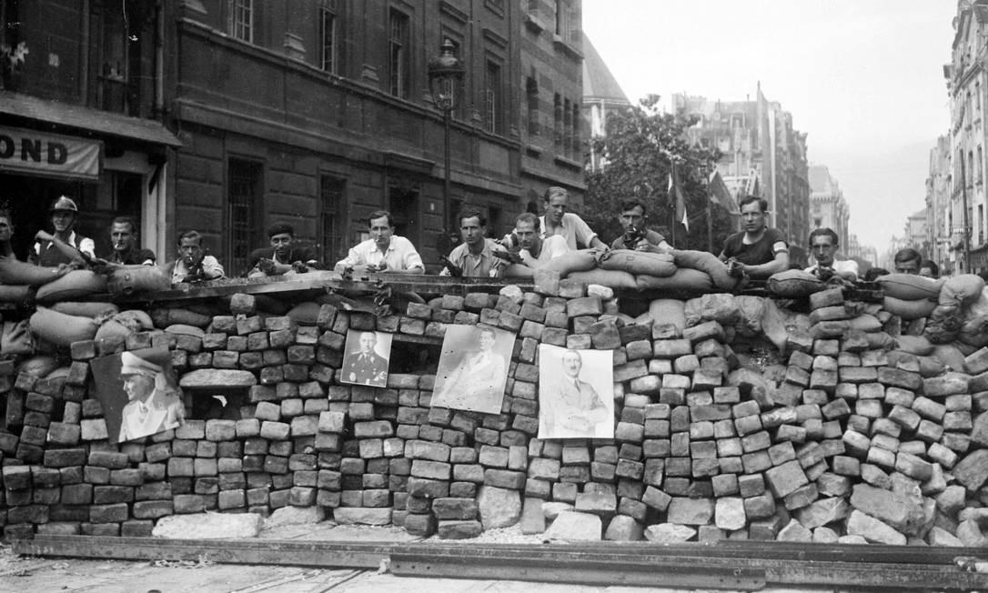 Integrantes das Forças Francesas do Interior (FFI) se posicionam atrás de uma barricada na qual estão pendurados retratos de nazistas na rua Saint-Jacques, em Paris, em 22 de agosto de 1944 Foto: - / AFP