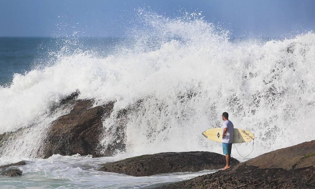 Surfista observa o mar errebentar nas pedras Foto: Fabiano Rocha / Agência O Globo