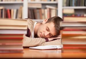 Homem dorme sobre livro em biblioteca Foto: Reprodução