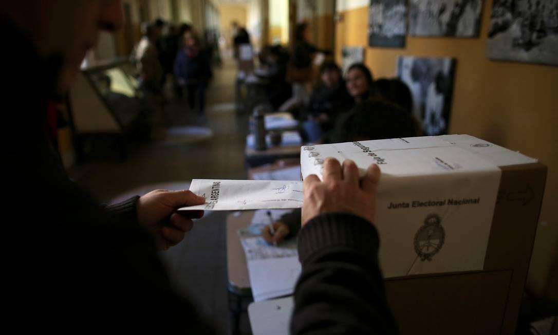 Um eleitor deposita seu voto em uma urna durante as eleições primárias realizadas neste domingo, na Argentina Foto: AGUSTIN MARCARIAN / REUTERS