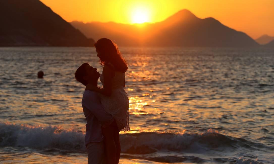 Sob a luz do sol que acaba de nascer, casal se abraça na Praia Vermelha Foto: Fabiano Rocha / Agência O Globo