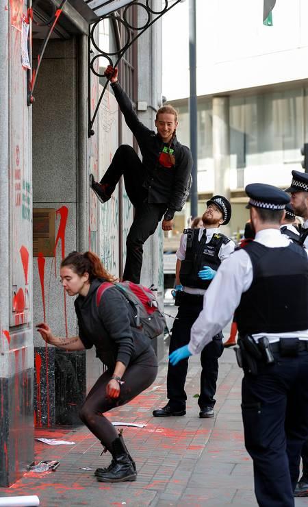 Policiais ingleses observam manifestantes escalando a fachada da embaixada Foto: PETER NICHOLLS / REUTERS
