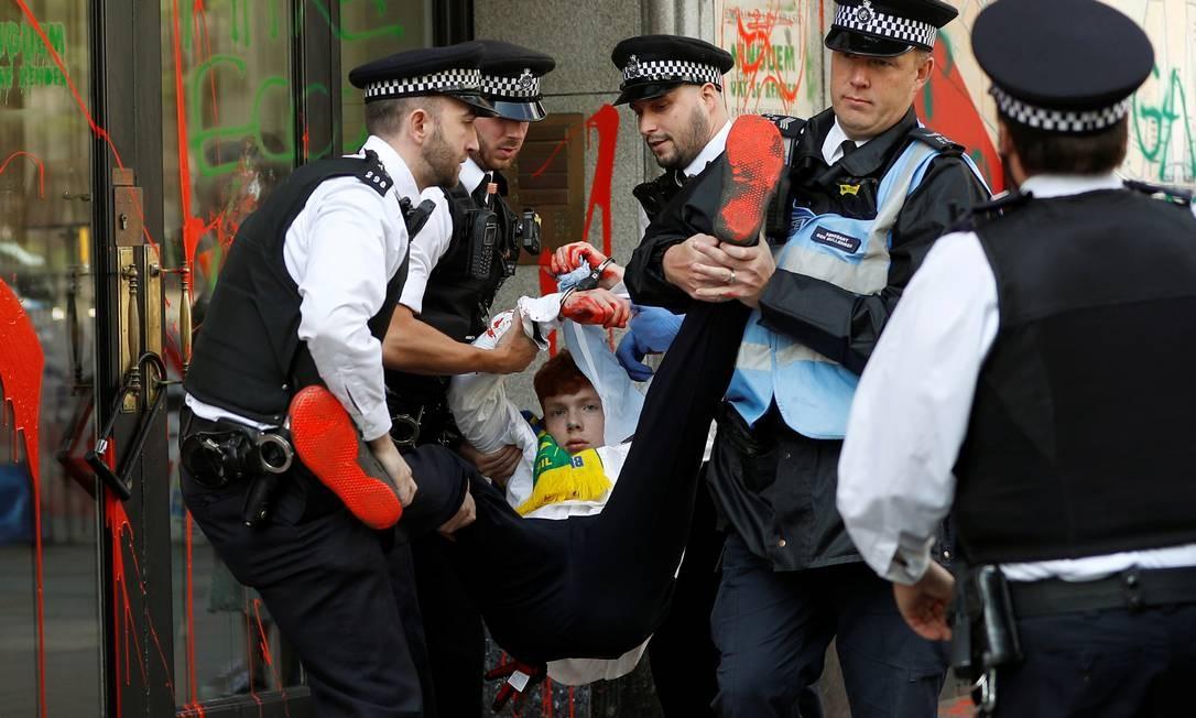Policiais retiram manifestante da porta da embaixada Foto: PETER NICHOLLS / REUTERS