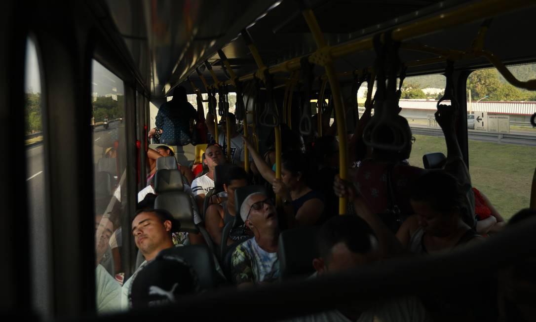 Quem consegue lugar para sentar aproveita o trajeto para cochilar Foto: Brenno Carvalho / Agência O Globo