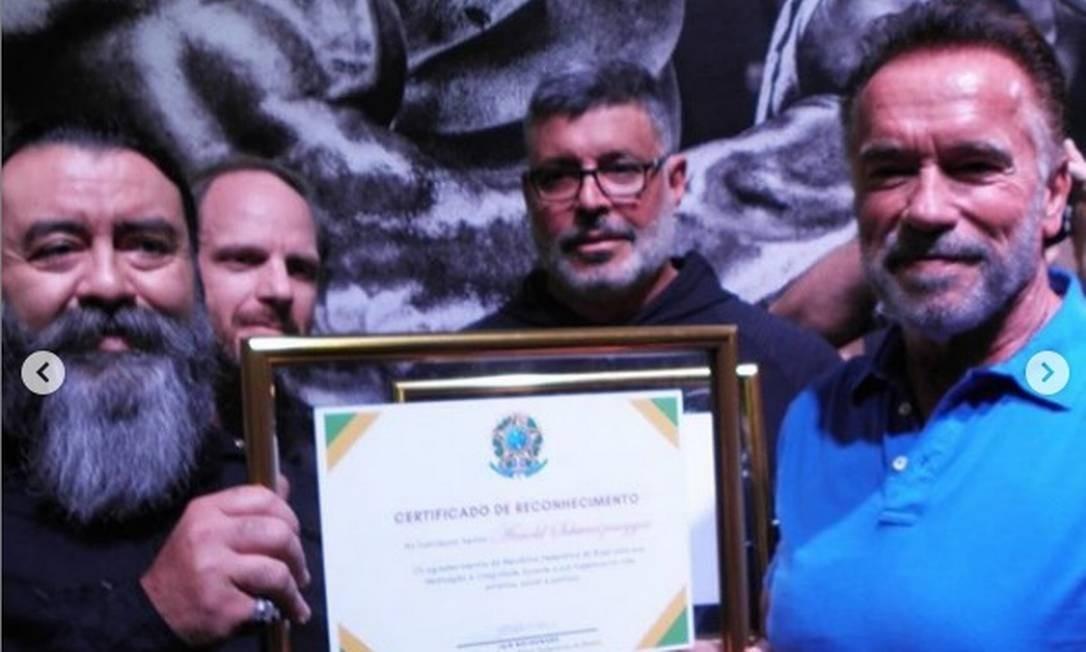 Frota entregou ao ator e ex-governador da Califórnia, Arnold Schwarzenegger, um certificado de reconhecimento assinado por Bolsonaro Foto: Reprodução
