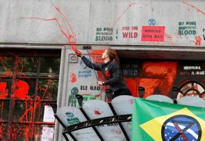 Ativista do grupo Extinction Rebellion joga tinta no prédio da Embaixada do Brasil em Londres, em protesto contra políticas do governo Bolsonaro para o meio ambiente Foto: PETER NICHOLLS / REUTERS