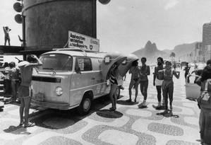 Verão de 83. Uma Kombi laranja da Telerj, com dois orelhões, mais catálogos e fichas, estacionada na Praia de Ipanema Foto: Otavio Magalhães / Arquivo O Globo / 8-1-1983
