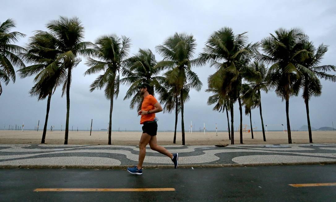 Chuva não atrapalha treino de corredor na orla de Copacabana Foto: Fabiano Rocha / Agência O Globo