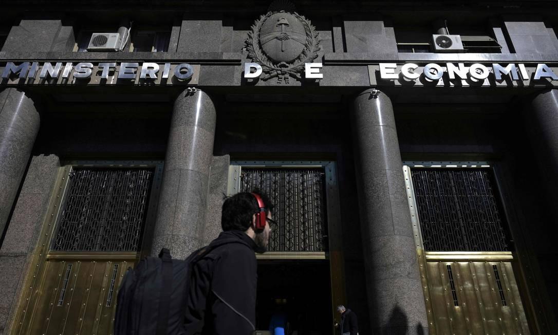 Um homem caminha em frente ao prédio do Ministério da Economia da Argentina. O presidente Mauricio Macri anunciou na quarta-feira aumentos salariais e cortes de impostos para ajudar a aliviar a economia Foto: JUAN MABROMATA / AFP