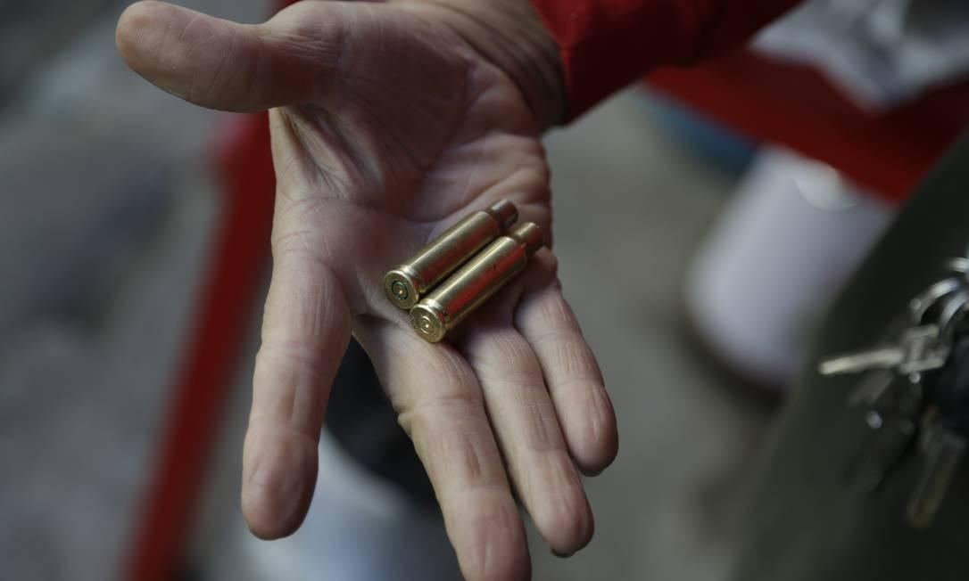 Morador mostra cápsulas de balas deflagradas após o tiroteio no Dona Marta Foto: Gabriel Paiva / Agência O Globo
