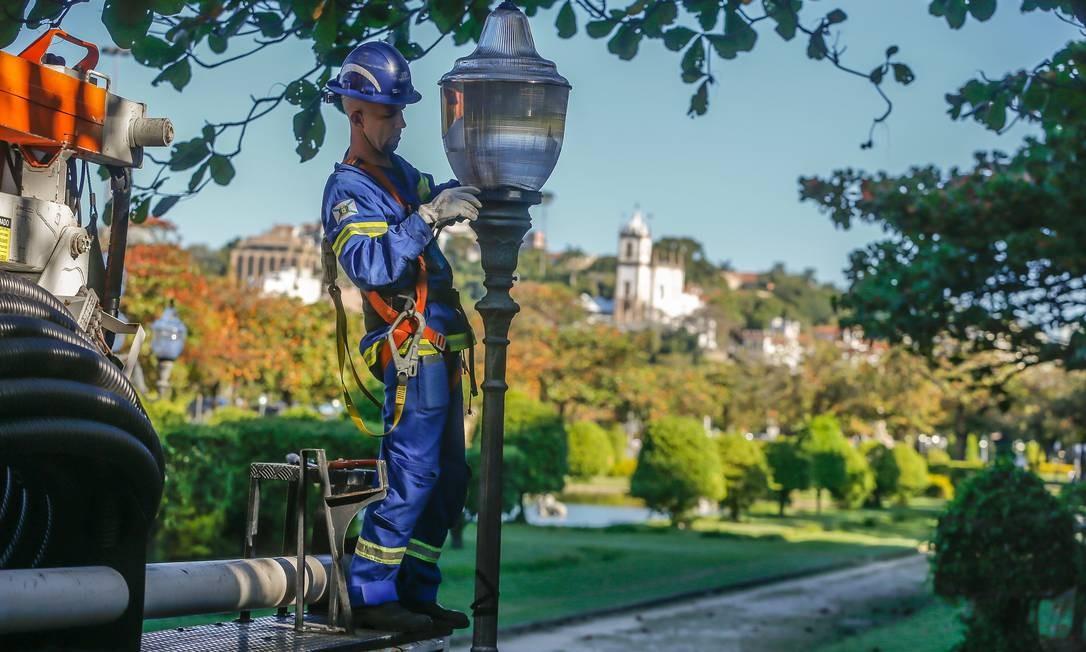 Funcionário da prefeitura repõe luminárias na Praça Paris, na Glória Foto: Marcelo Regua / Agência O Globo