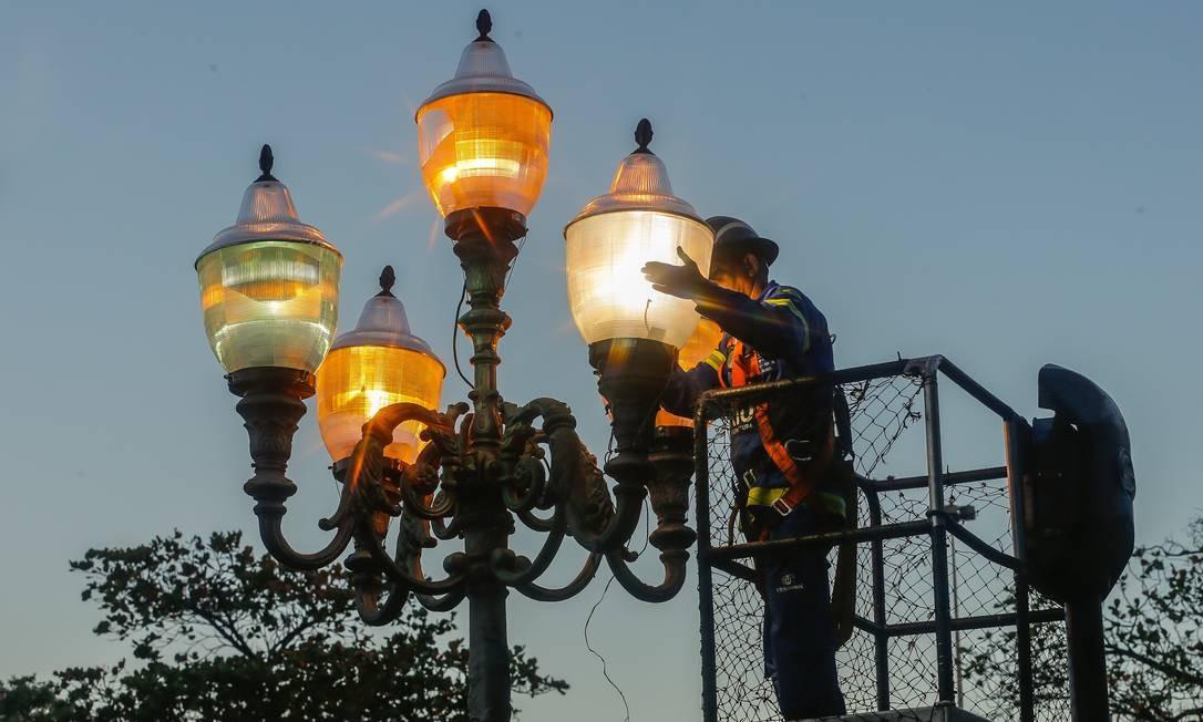 Funcionário da prefeitura repõe luminárias na Praça Paris, na Glória, após ação de vandalismo destruir peças Foto: Marcelo Regua / Agência O Globo