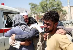 Afegãos se consolam durante o funeral de seus parentes após atentado suicida Foto: OMAR SOBHANI / REUTERS