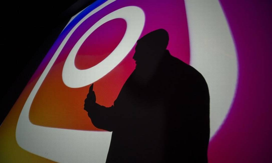 Homem em frente a um mural do Instagram Foto: Aytac Unal / Anadolu Agency | Getty Images