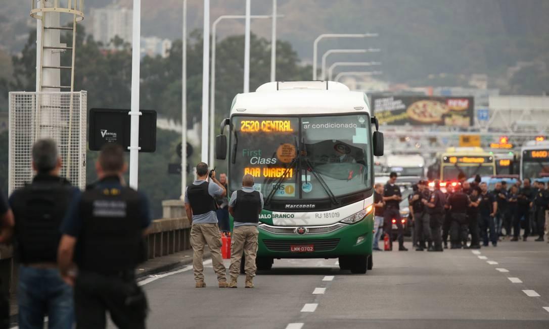 Policiais cercam o ônibus Foto: Fabiano Rocha / Agência O Globo