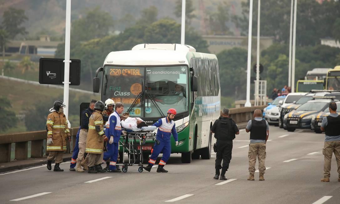 Refém é levado por policiais e equipe médica da Concessionária Foto: Fabiano Rocha / Agência O Globo