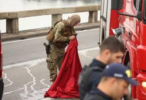 Policial prepara manta vermelha para se camuflar em cima de veículo dos bombeiros Foto: Fabiano Rocha / Agência O Globo