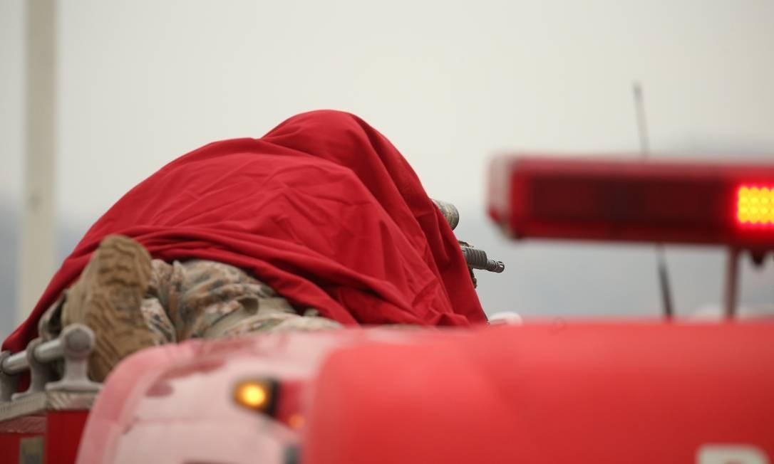 Já em cima do veículo, atirador se posiciona Foto: Fabiano Rocha / Agência O Globo