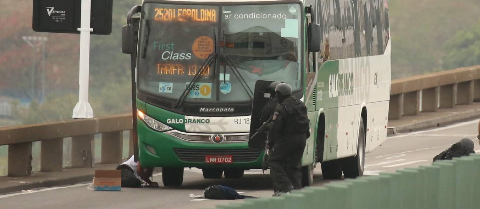 Policiais militares se aproximam do sequestrador já caído no chão após ser baleado Foto: Fabiano Rocha / Agência O Globo