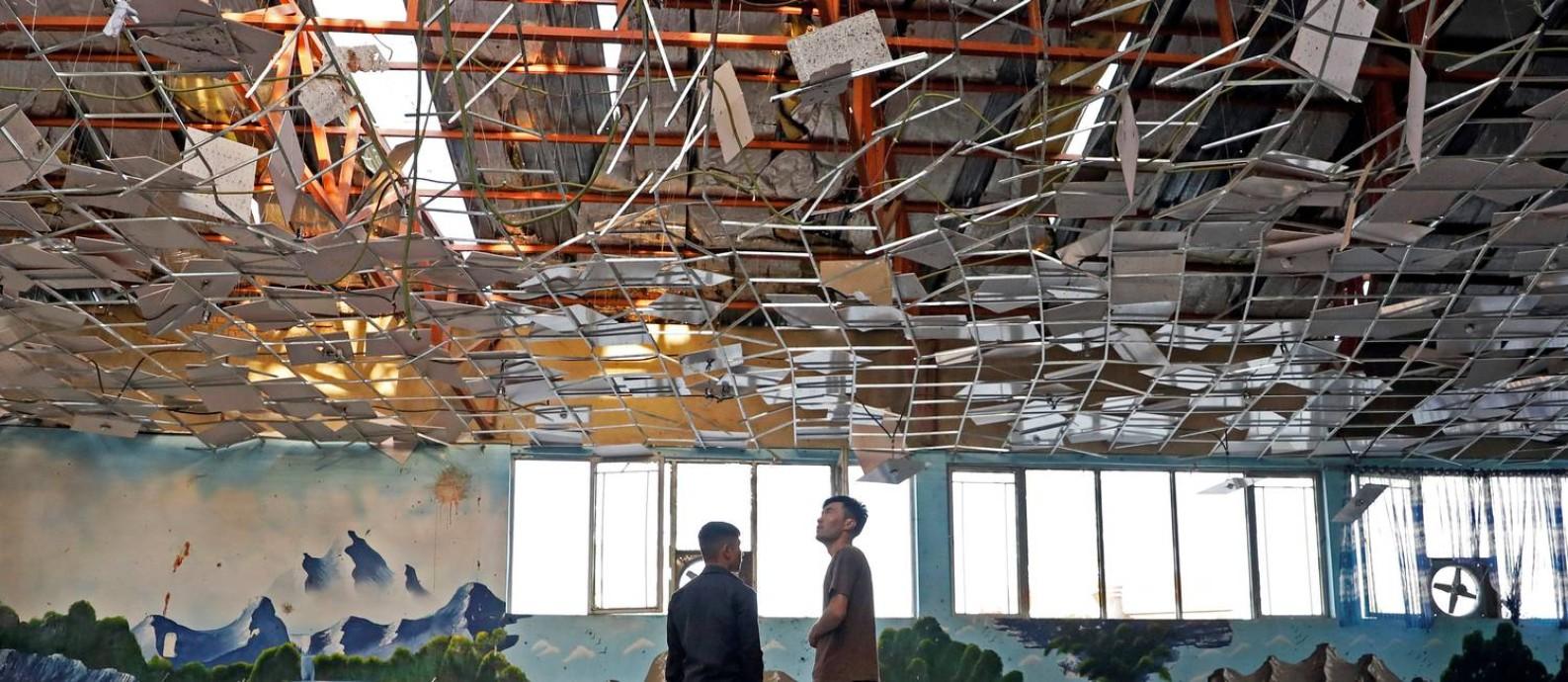 Trabalhadores inspecionam salão de festas onde 63 pessoas foram mortas em um atentado no fim de semana em Cabul. Ataque foi realizado pelo grupo Estado Islâmico Foto: MOHAMMAD ISMAIL / REUTERS