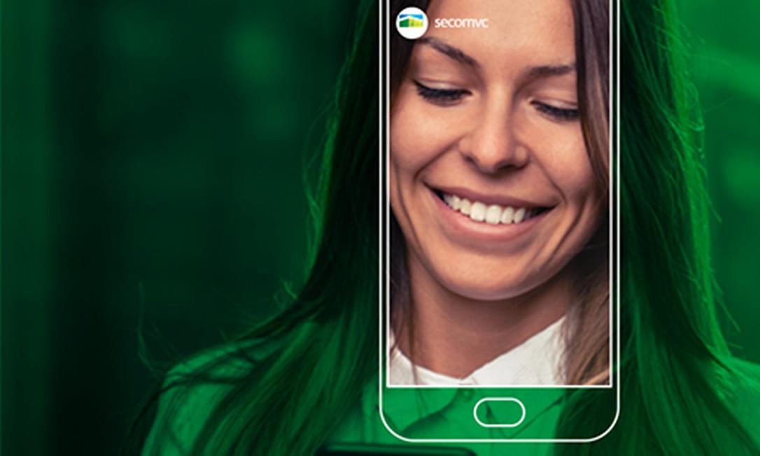 Identidade visual do 'SecomVC' inclui mulher sorrindo ao olhar um aparelho celular Foto: Divulgação