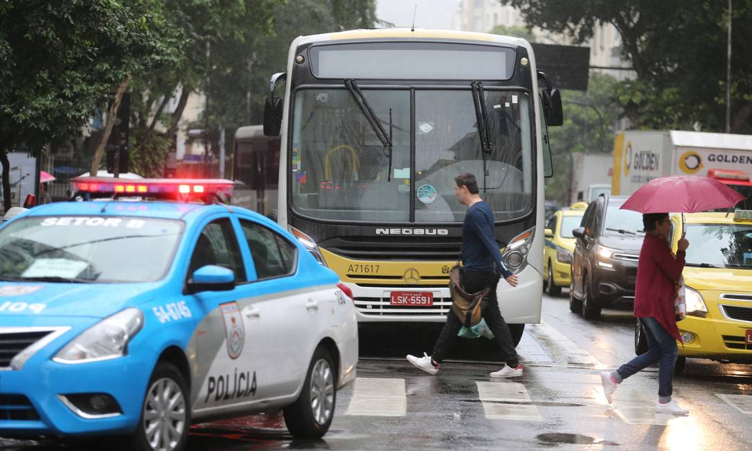 Ônibus que foi alvo do ataque fica parado na Rua Barata Ribeiro. Um pouco à frente, um carro da Polícia Militar Foto: Marcia Foletto / Agência O Globo