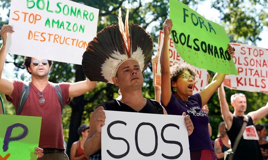 Em Berlim, na Alemanha, manifestante se caracterizou de indígena e levou cartaz de S.O.S, símbolo internacional de socorro, pedindo pela proteção da Amazônia Foto: ODD ANDERSEN / AFP