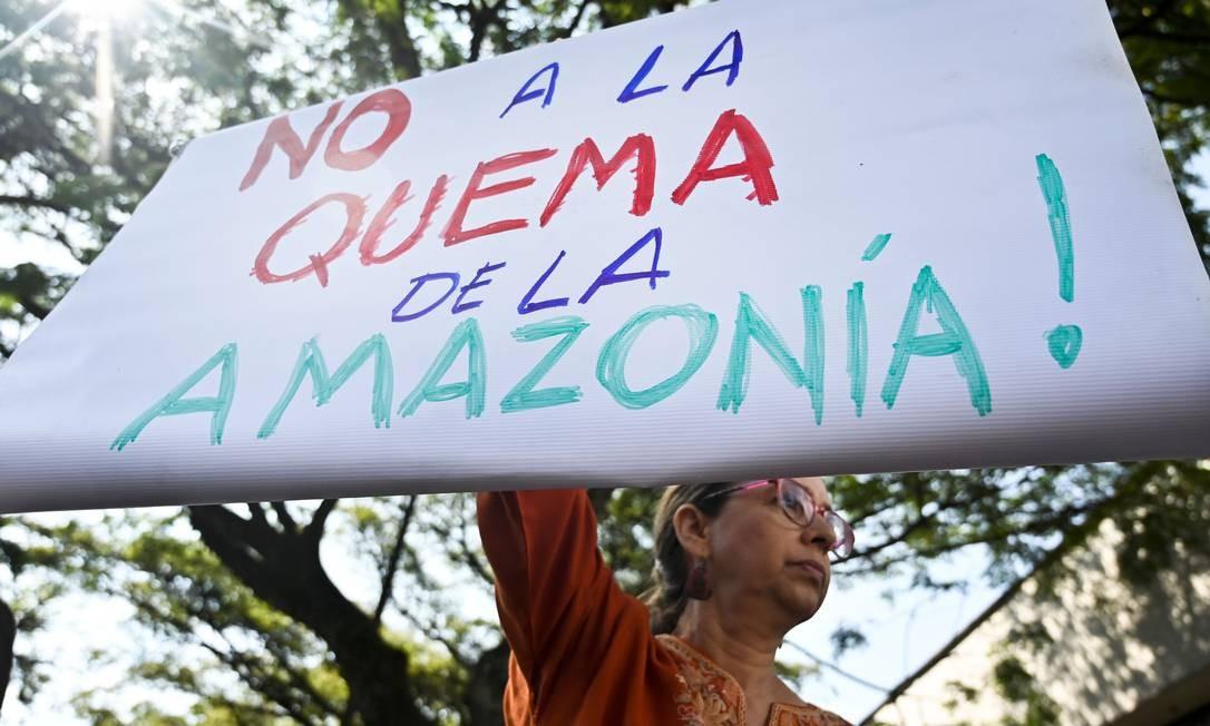 """Ativista segura placa com a frase """"Não à queima da Amazônia"""" durante protesto contra as queimadas na Amazônia em frente ao consulado brasileiro em Cali, Colômbia. Foto: Luis Robayo / AFP"""
