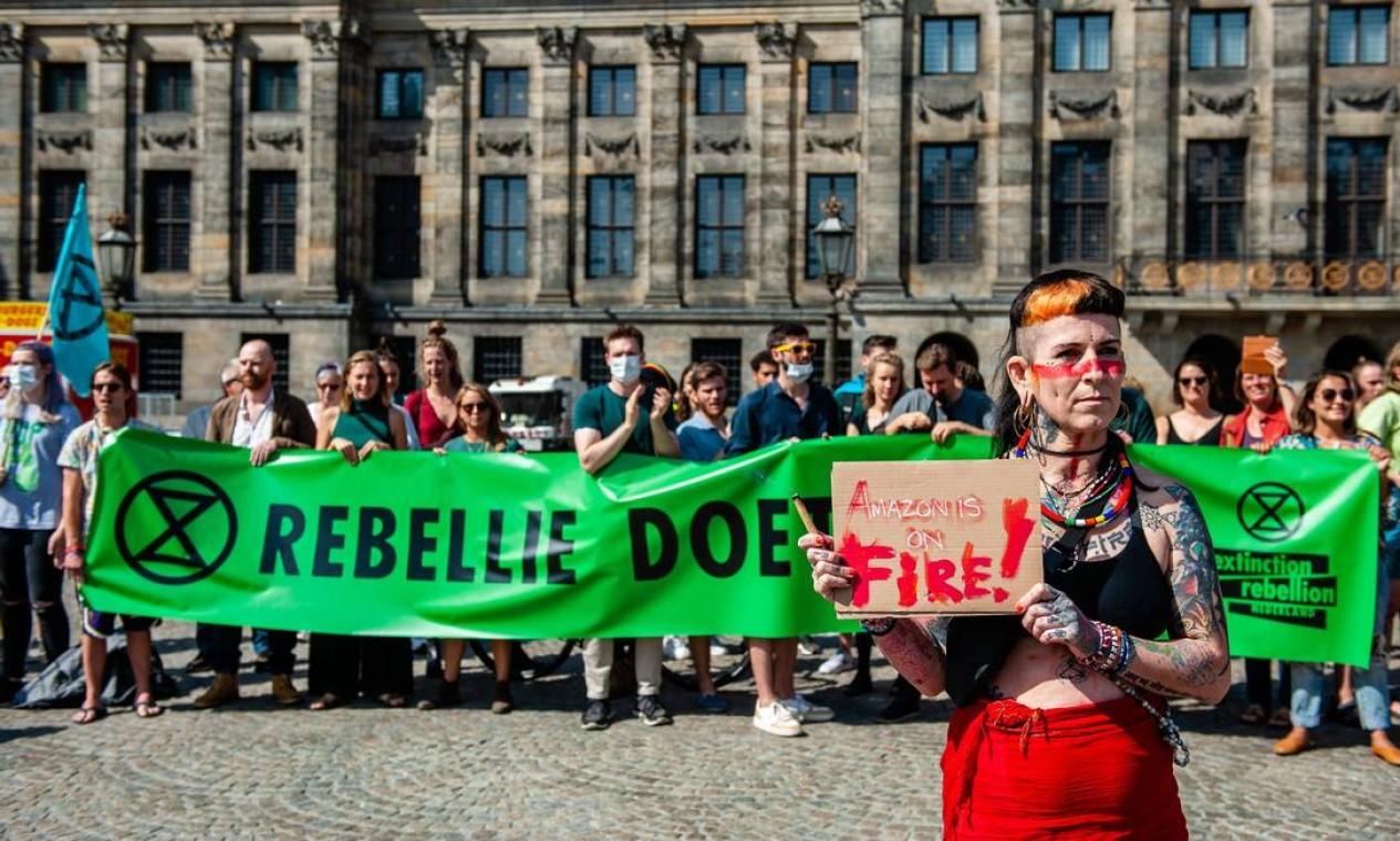 Ativistas da Rebelião da Extinção protestam em Amsterdã pedindo proteção para a floresta amazônica. desmatamento e do fogo. Números oficiais mais recentes mostram que mais de 76 mil incêndios florestais foram registrados no Brasil até o momento Foto: RomyFernandez / AFP