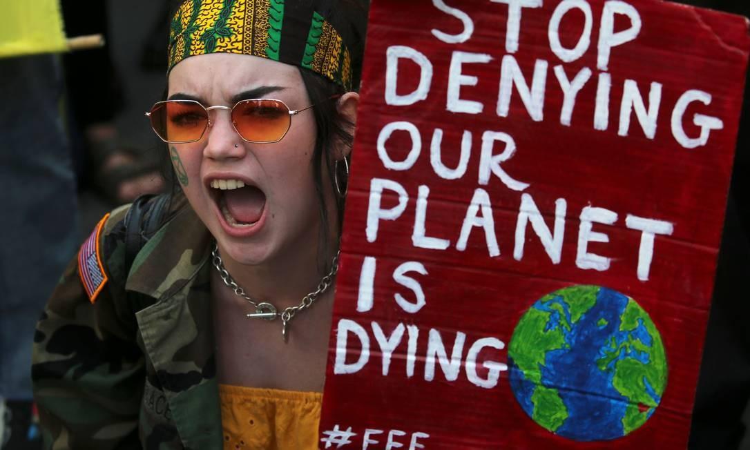 """Manifestante segura cartaz que diz """"pare de negar que nosso planeta está morrendo"""" durante manifestação no centro de Londres Foto: ISABEL INFANTES / AFP"""