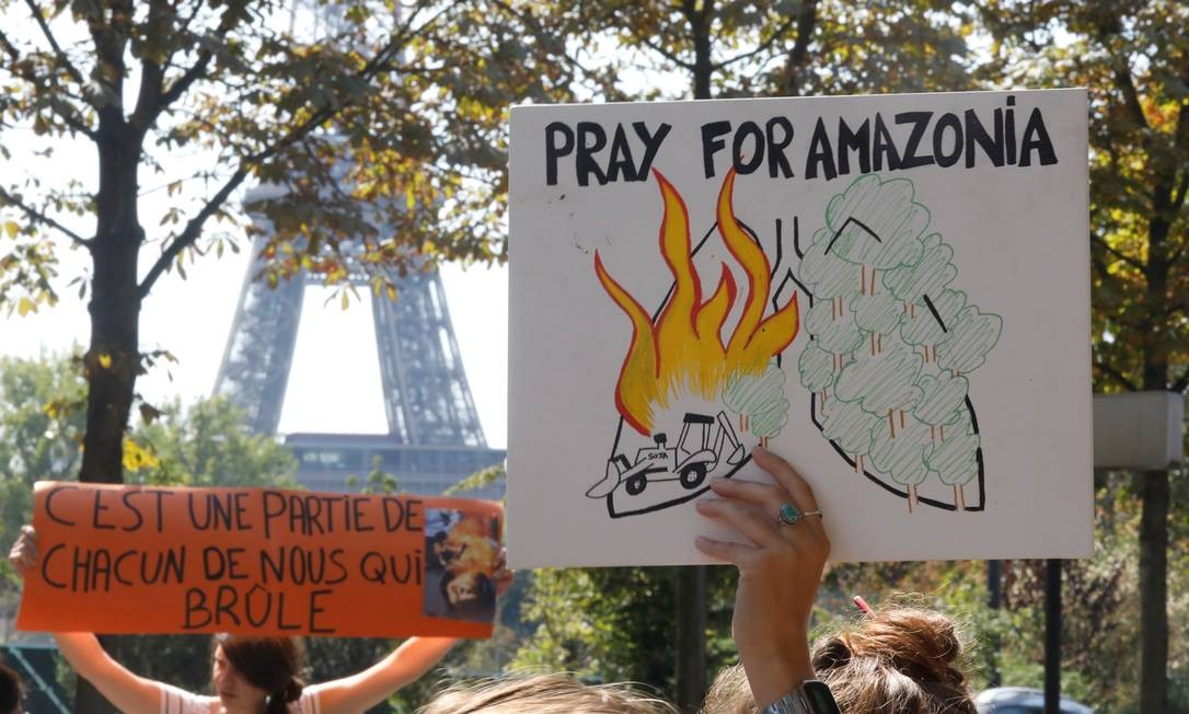 """Manifestantes erquem cartazes com os dizeres """"Ore pela Amazônia"""" e """"É uma parte de cada um de nós que queima"""" durante protesto em Paris, na França, em frente à embaixada brasileira Foto: CHARLES PLATIAU / REUTERS"""