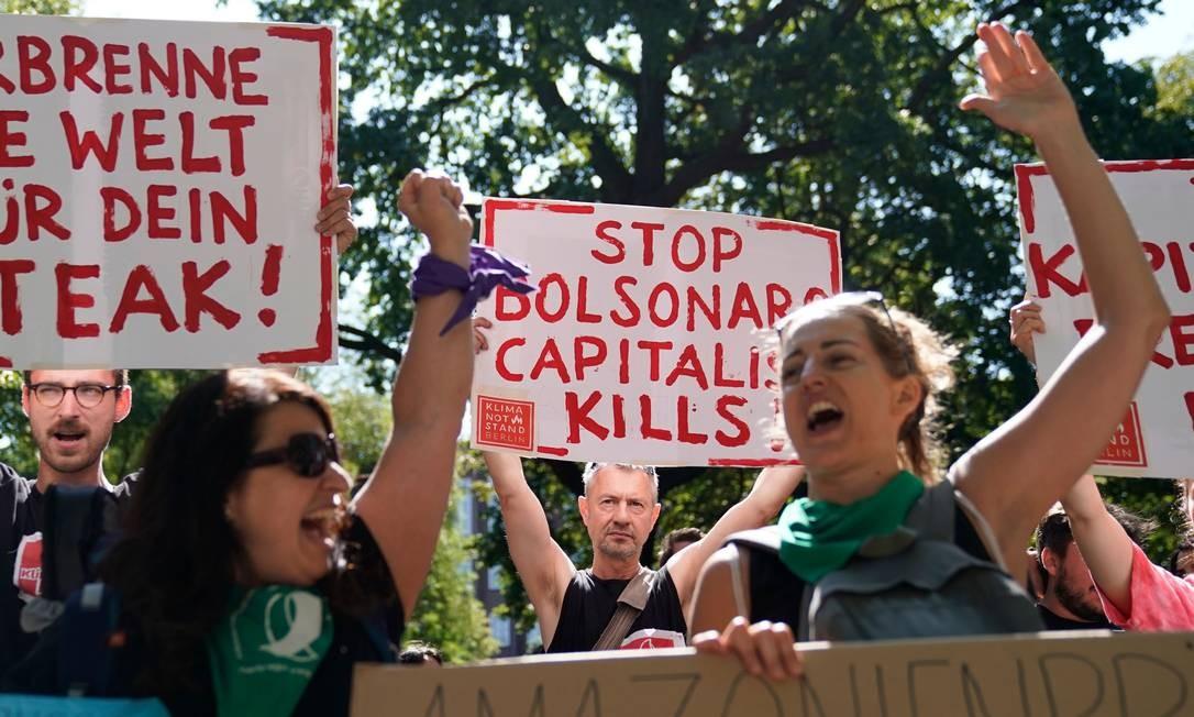 """Manifestantes em Berlim, na Alemanha, exibem cartazes durante uma manifestação contra o desmatamento na Amazônia e as políticas ambientais do governo Bolsonaro. Incêndios na Amazônia constituem uma """"situação urgente"""" que deve ser discutida durante a cúpula do G7 este final de semana, disse a porta-voz da chanceler Angela Merkel Foto: ODD ANDERSEN / AFP"""
