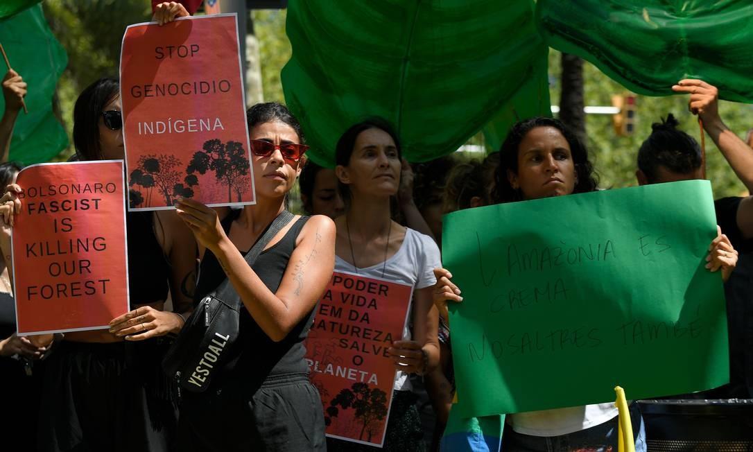 """Ativistas exibem cartaz com a inscrição """"Pare o genocídio dos povos indígenas"""" durante uma manifestação em Barcelona Foto: LLUIS GENE / AFP"""
