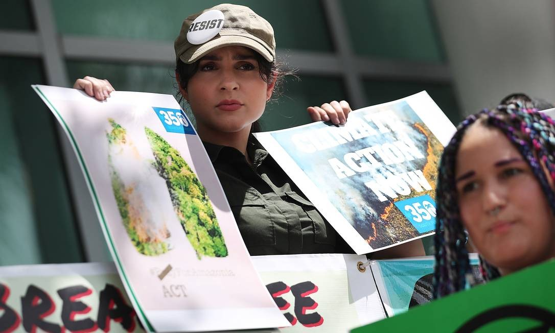 A blogueira cubana Yadira Escobar, que reside em Miami, na Flória, se junta a ativistas como que protestam pela proteção da floresta amazônica em frente ao consulado brasileiro em Coral Gables Foto: JOE RAEDLE / AFP