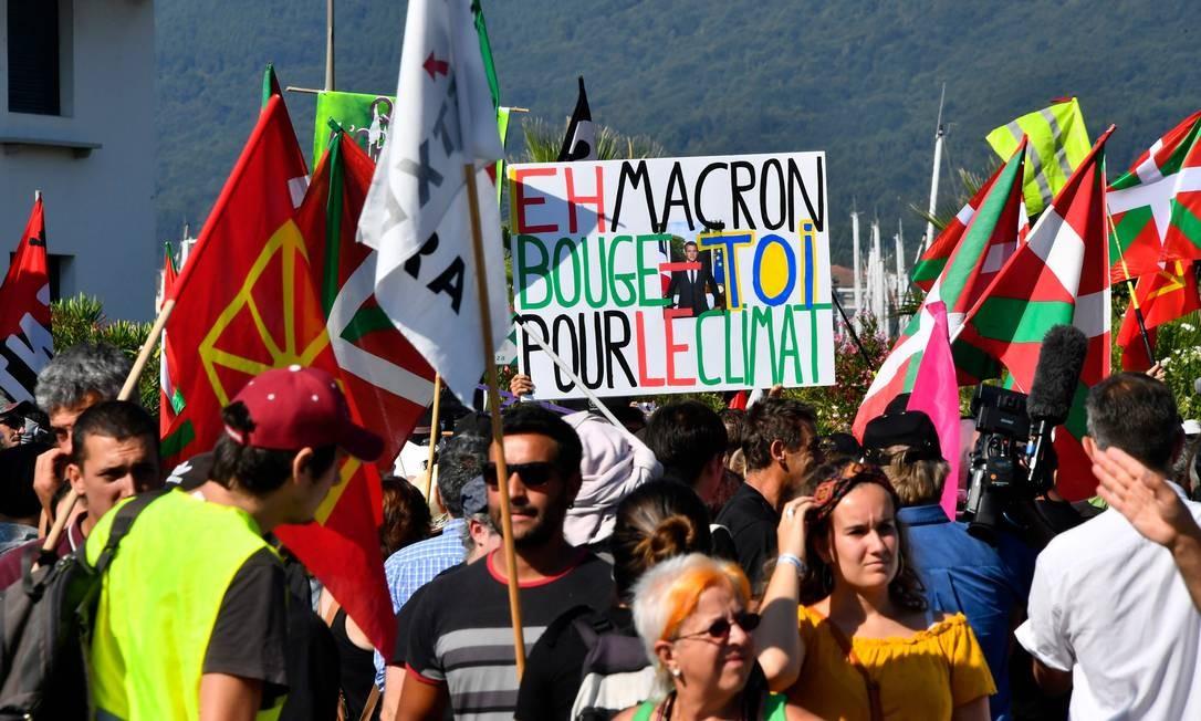 """Um manifestante segura um cartaz com a frase """"Ei Macron, mova-se pelo clima"""" enquanto outros seguram bandeiras bascas durante protesto na França Foto: Georges Gobet / AFP"""