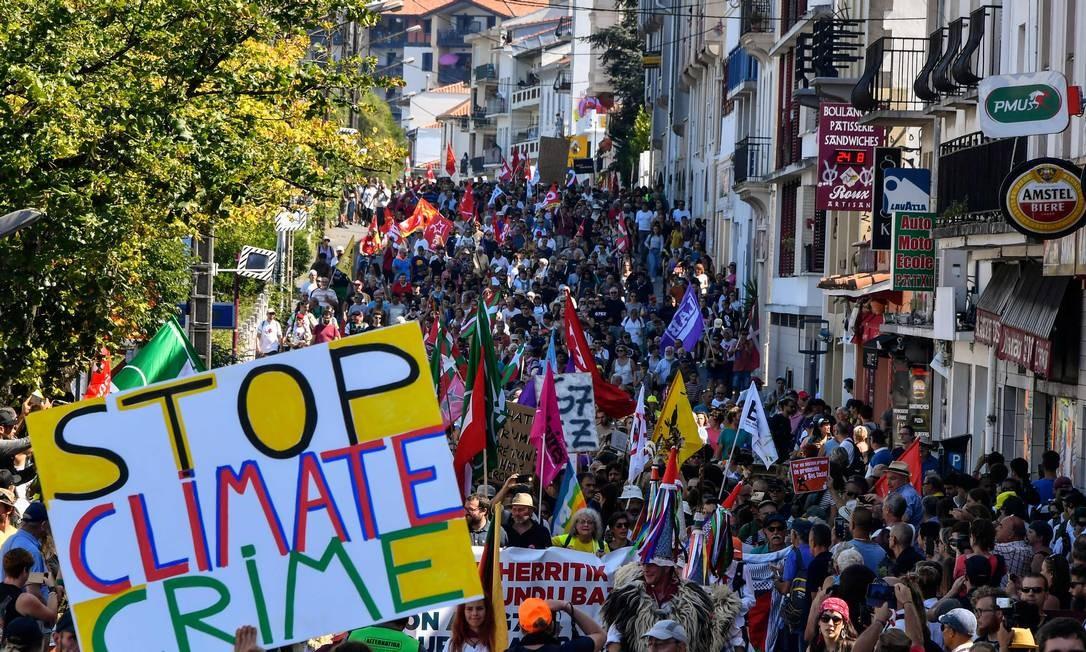 Milhares de manifestantes começaram a reunir-se a cerca de 30 quilômetros ao sul da sede do encontro do G7. As bandeiras acenam acima de uma multidão que inclui causas que vão dos direitos dos homossexuais à Palestina Foto: Georges Gobet / AFP