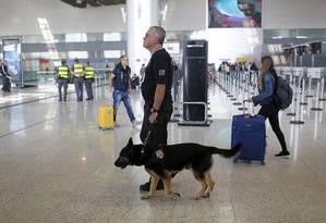 Policial federal caminha com cachorro no terminal 3 do aeroporto de Guarulhos Foto: Edilson Dantas 26/07/2016 / Agência O Globo