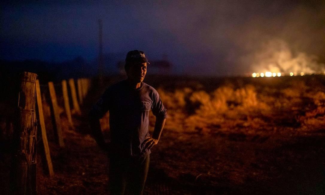 Homem olha para incêndio na fazenda onde trabalha no município de Nova Santa Helena, estado do Mato Grosso - 23/08/2019 Foto: JOAO LAET / AFP