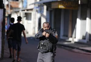 Policial com fuzil durante operação no Rio: na cidade, houve queda de assassinatos, mas total de autos de resistência é o maior da série histórica, segundo o ISP. Nos primeiros sete meses deste ano, houve 1.075 registros Foto: Pablo Jacob