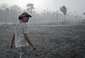 O agricultor Aurelio Andrade caminha por uma área queimada da floresta amazônica, perto de Porto Velho, capital de Rondônia Foto: CARL DE SOUZA / AFP