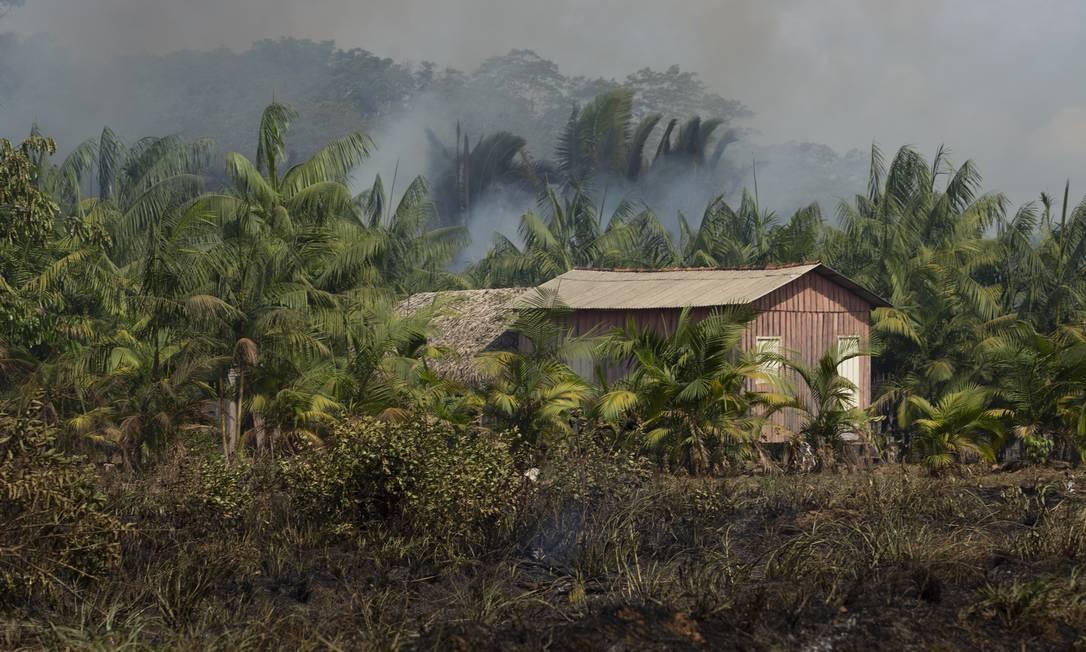 A floresta queimando no entorno de uma construção que fica à beira da BR-319, perto de Vila Realidade. A vila fica a 600 km de Manaus e 290 km de Porto Velho Foto: Gabriel Monteiro / Agência O Globo