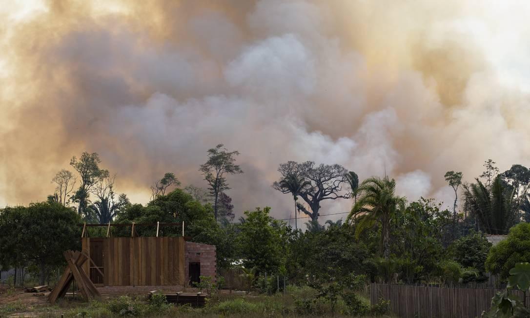 A fumaça do fogo que consome a floresta perto de uma construção inacabada. A reconstrução da estrada vai permitir o acesso a áreas ide florestas primárias contínuas na Amazônia Central e Norte. Foto: Gabriel Monteiro / Agência O Globo