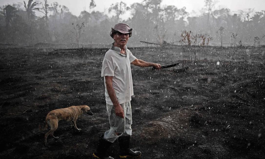 O agricultor Aurelio Andrade caminha em área queimada da Floresta Amazônica: ele diz que desmata para sobreviver Foto: CARL DE SOUZA / AFP