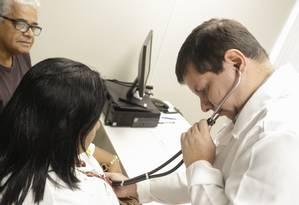 O clínico geral Rafael Pires Nemer atende Denise sob o olhar atento de seu marido Fernando Antônio da Silva: ela participa do programa de emagrecimento saudável Foto: Gabriel de Paiva